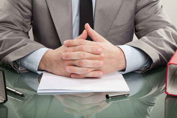 A man with hands folded on a desk (business interruption insurance)
