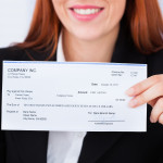 Smiling Businesswoman Holding Cheque