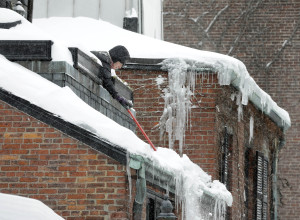 Boston homeowner clears roof. Insurers and agents are fielding ice dam questions and claims. (AP Photo/Steven Senne)