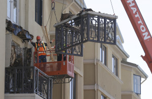 Workers remove part of a balcony that collapsed at the Library Gardens apartment complex in Berkeley, Calif., Tuesday, (AP Photo/Jeff Chiu)