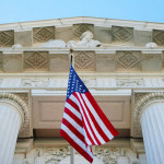 American flag by a justice building with columns