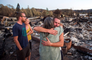 Charlie Liethen, right, embraces Sharon Dawson, who lost her home in a wildfire, in Middletown, Calif., on Monday. More than 2,000 homes had been confirmed destroyed, with the number likely to go higher as assessment continues. (AP Photo/Noah Berger)