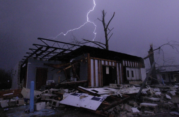 Lightning illuminates a house after a tornado touched down in Jefferson County, Ala., damaging several houses, Friday, Dec. 25, 2015, in Birmingham, Ala. A Christmastime wave of severe weather continued Friday. (AP Photo/Butch Dill)