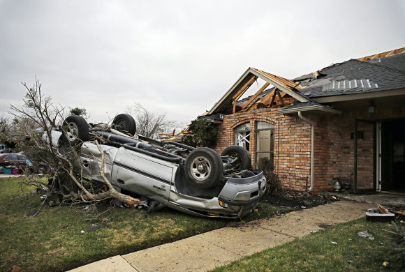 A car sits on the front lawn of a home Monday, Dec. 28, 2015, in Garland, Texas. Residents surveyed the destruction from deadly tornadoes in North Texas as the same storm system brought winter woes to the Midwest on Monday, amplifying flooding that's blamed for more than a dozen deaths and prompting hundreds of flight cancellations. (G.J. McCarthy/The Dallas Morning News via AP)