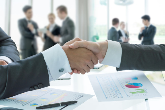 Business hand shake, business situation with people in background