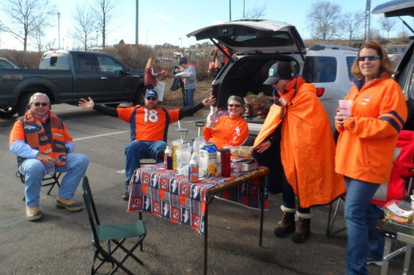 Dave Adams, in the Manning jersey, and Pam Adams, in the orange cape, are brother and sister owners of ISU Insurance Services of Colorado Inc. Here they are at a tailgate party with friends at Mile High stadium before the AFC Championship game in which the Broncos advanced against the New England Patriots in a 20-18 duel.