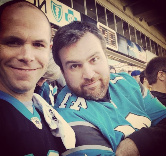 H. Garrett Droege, executive director of TechAssure Association Inc. in Charlotte, N.C., right, with a client at the Panthers vs. Arizona Cardinals game.