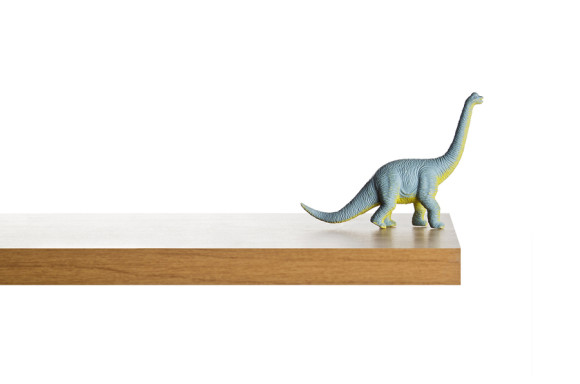 Dinosaur figurine placed on a ledge against a white background ** Note: Slight blurriness, best at smaller sizes