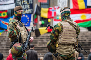 Belgian soldiers guard a memorial site at the Place de la Bourse in Brussels, Sunday, March 27, 2016. In a sign of the tensions in the Belgian capital and the way security services are stretched across the country, Belgium's interior minister appealed to residents not to march Sunday in Brussels in solidarity with the victims. (AP Photo/Geert Vanden Wijngaert)