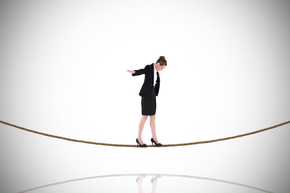 Businesswoman performing a balancing act on tightrope against white background with vignette