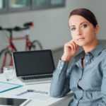 Businesswoman sitting at office desk and posing