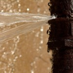An old pipe has burst in winter, and water squirts out with lots of splashes