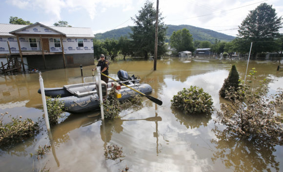 Lt. Dennis Feazell, of the West Virginia Department of Natural Resources, keeps his boat on station as he and a co-worker search flooded homes in Rainelle, W. Va., Saturday, June 25, 2016. Heavy rains that pummeled West Virginia left multiple people dead, and authorities said Saturday that an unknown number of people in the hardest-hit county remained unaccounted for. (AP Photo/Steve Helber)