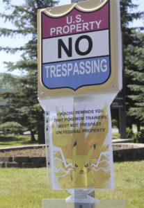 A sign at the National Weather Service in Anchorage, Alaska, informs Pokemon players that it's illegal to trespass on federal property. The staff started noticing an uptick of people in the parking lot after the location was included as a gym in the popular game. (AP Photo/Mark Thiessen)