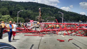 A giant crane sits road bed of the Tappan Zee Bridge north of New York City after toppling around noon on Tuesday, July 19, 2016, during construction of a new bridge, across the Hudson River between Westchester and Rockland counties. The base and treads of the huge, moveable crane sat on the unfinished new bridge while part of the toppled crane lay across the lanes of the old bridge and another section lay across a construction platform in the water between the two spans. (David Leibstein via AP)