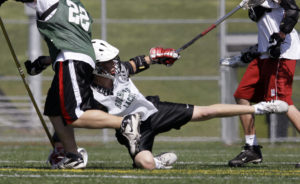 In this May 17, 2009, photo a high school lacrosse player falls onto a field of synthetic turf during practice in north Seattle. On the turf bits of ground-up tires are used as filler between the blades of artificial grass. Now the government is reconsidering whether sports fields and playgrounds made from ground-up tires can harm children's health after some Environmental Protection Agency scientists raised concerns, according to internal EPA documents. (AP Photo/Elaine Thompson, file)