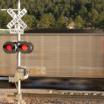 Motion blurred locomotive at railroad crossing with signal box