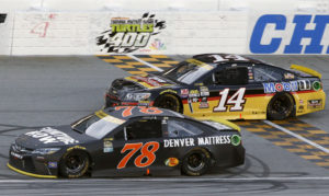 Martin Truex Jr. (78) drives past Tony Stewart (14) during a NASCAR Sprint Cup Series auto race at Chicagoland Speedway, Sunday, Sept. 18, 2016, in Joliet, Ill. (AP Photo/Nam Y. Huh)