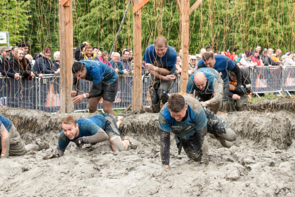 Boughton House Northamptonshire UK - May 31 2015: Team MNDA endures the shocking treatment of the electroshock therapy obstacle at the Tough Mudder extreme sport challenge raising funds for Help for Heroes.