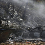 In this Nov. 10, 2015, file photo, a charred car and aircraft debris smolder where a small business jet crashed into an apartment building in Akron, Ohio. The National Transportation Safety Board is scheduled to meet in Washington on Tuesday, Oct. 18, 2016, to decide the probable cause of a corporate jet crash that killed the two pilots and seven passengers, and occurred within two miles of Akron Fulton International Airport while descending for landing. No one on the ground was injured. (Ed Suba Jr./Akron Beacon Journal via AP, File)