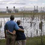 In this April 25, 2014, file photo, Bryant Gobble, left, embraces his wife, Sherry Gobble, right, as they look from their yard across an ash pond full of dead trees toward Duke Energy's Buck Steam Station in Dukeville, N.C. North Carolina officials are advising dozens of residents near Duke Energy coal ash sumps not to drink or cook with water from their wells after tests showed contamination with toxic heavy metals. (AP Photo/Chuck Burton, File)