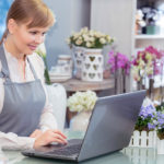 Flower business in action. Small business entrepreneur florist managing her business working by her laptop