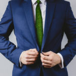 Man dressed in business suit and green leaves as tie representing a natural job in defense of a green environment.