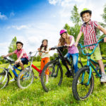 Happy kids in colorful bike helmets holding bike handle-bars and are ready to ride their bikes in green field in summer
