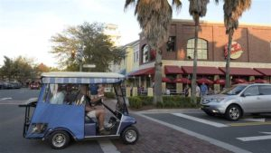 Residents ride their golf cart on a street at the Lake Sumter Landing Market Square in The Villages, Florida. Growing numbers of seniors in some areas are using golf carts and mixing with traffic on public roads, which worries safety experts. © The Associated Press