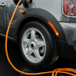 Electric car battery charging with orange wire. ** Note: Slight blurriness, best at smaller sizes