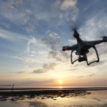 Remote controlled drone Dji Phantom 3 equipped with high resolution video camera flying above the beach against a sunset.