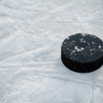 Hockey puck on ice hockey rink with copy space for text. Winter sport concept.
