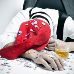 a man with a santa hat and covered with confetti sleeping in his desk after an office christmas party