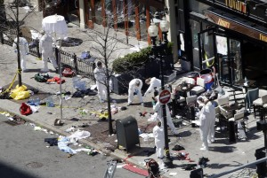 Investigators in haz-mat suits examine the scene of the second bombing on Boylston Street in Boston Tuesday, April 16, 2013 near the finish line of the 2013 Boston Marathon. (AP Photo/Elise Amendola)