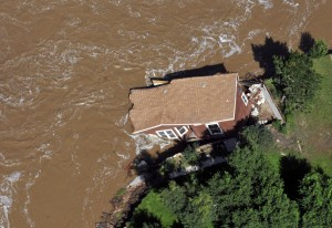 In this aerial photo, a home is pulled into the fast currents of the flooded South Platte River off of U.S 34 between Greeley and Kersey, Colo., Monday, Sept. 16, 2013. Weary Colorado evacuees have begun returning home after days of rain and flooding, but Monday's clearing skies and receding waters revealed only more heartbreak: toppled houses, upended vehicles and a stinking layer of muck covering everything. (AP Photo/The Greeley Tribune, Joshua Polson)